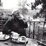 Picture in black and white of Ferenc Gogos smocking a cigarette on a terrasse