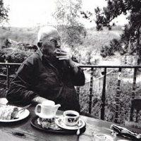 Foto in zwart-wit van Ferenc Gogos die een sigaret smokt op een terras